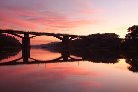 Railway bridge connecting river banks with reflection at sunrise photo