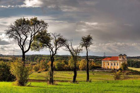 Autumn on the pasture near the church before rain photo