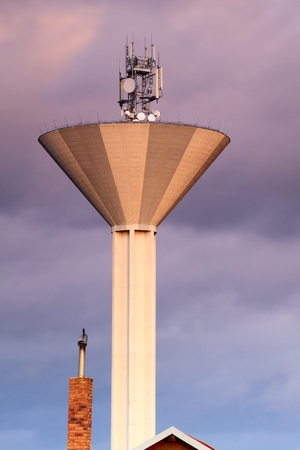 Modern water tank tower with communications antennas photo