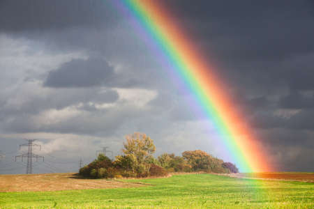 Natural rainbow over green field and dark sky Stock Photo - 12196391