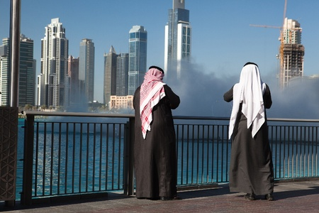 Two Dubai sheiks in front of fountain before Burj Khalifa, Dubai United Arab Emirates