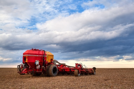Seeding machine on the empty field at sunset photo