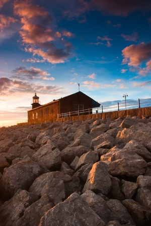 Lighthouse on the pier - Scenic view of rocky sea defences, Morecambe, Lancashire, England, Stock Photo