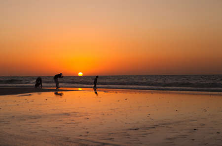 The silhouettes people at the sunset background Stock Photo - 14763409