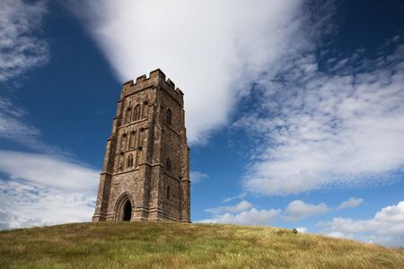 Tourists exploring the ruins of St  Michael s Tower at the top of glastonbury tor in sommerest england  photo