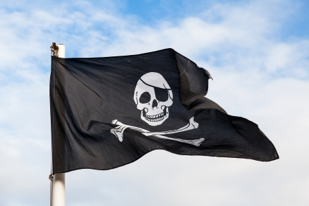 sea robber: Waving Pirate flag isolated on blue sky  Stock Photo