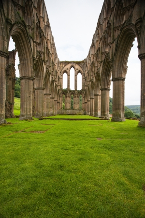 abbeys: Scenic view of ruins of Rievaulx Abbey under cloudscape, North Yorkshire Moors, National Park, England