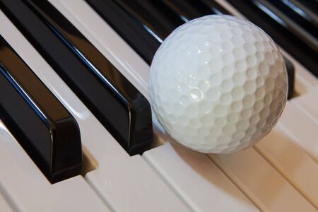 Golf ball and piano keyboards photo