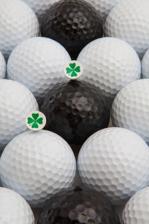 Different golf balls and wooden tees with four leaf clovers photo