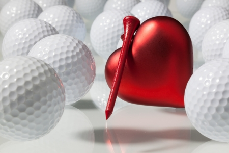 White golf balls and red heart on a glass table