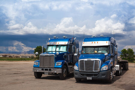 Two typical american blue Freightliner trucks on a parking place before storm in Utah