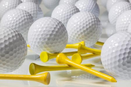 Různé golfové míčky na skleněný stůl