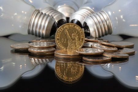 wasteful: Wasteful bulbs and U S  dollar coins on a black table Stock Photo