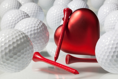 Bílé golfové míčky a červené srdce na skleněný stůl