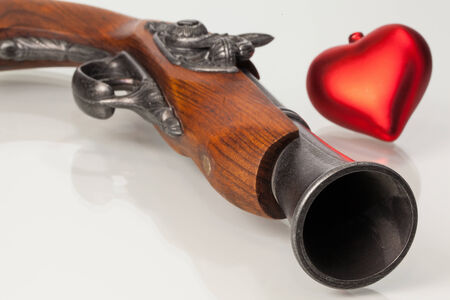 inoffensive: Old gun and red heart on the glass desk