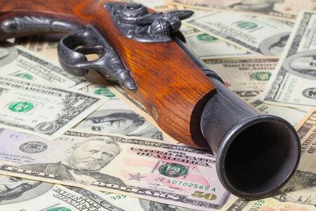 flint gun: Old gun and dollar bills on the table