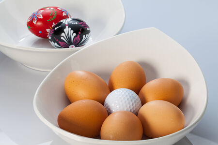 Two white ceramics bowls,easter eggs and golf balls photo
