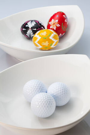 Two white ceramics bowls,golf balls and easter eggs photo