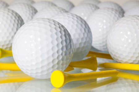 Different golf balls on a glass table