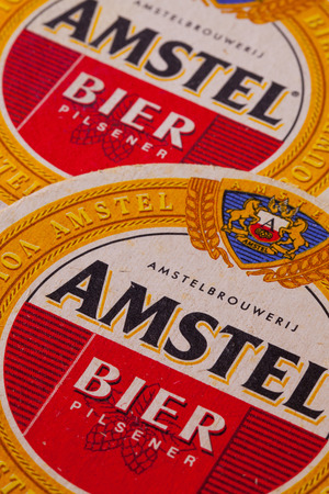 amstel: ENGLAND,LONDON - November 11, 2014:Beermats from Amstel beer.Amstel Brewery is a Dutch brewery founded in 1870 on the Mauritskade in Amsterdam