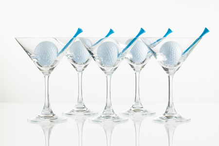 Five glasses of champagne and golf equipments on the glass desk