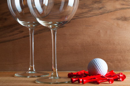 Two glasses  of wine and golf equipments on the wooden background from real wood veneer with interesting growth 写真素材