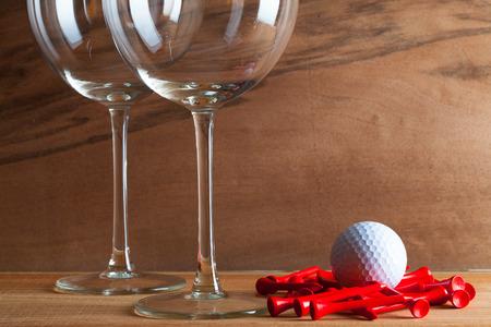 Dvě sklenky vína a golfových zařízení na dřevěné pozadí z pravého dřeva dýhy se zajímavým růstem Reklamní fotografie