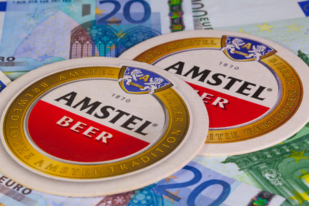 amstel: England,London - November 11, 2014:Beermats from Amstel beer and eur money.Amstel Brewery is a Dutch brewery founded in 1870 on the Mauritskade in Amsterdam Editorial
