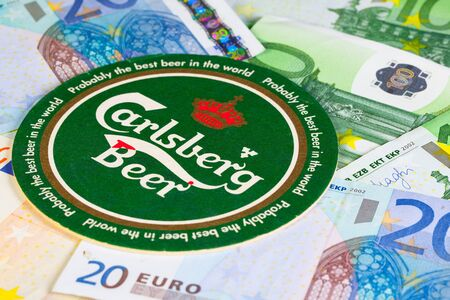 carlsberg: England, London - November 11, 2014:Beermat from Carlsberg beer and eur money.The Carlsberg is a Danish brewing company founded in 1847 by J. C. Jacobsen with headquarters located in Copenhagen,Denmark