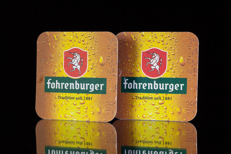 illustrative material: GERMANY,BERLIN - January  7,2015:Beermats from Fohrenburger beer.It was more than 120 years ago when Fohrenburger Beer founder Ferdinand Gassner was not happy about the beer he received in his restaurant.