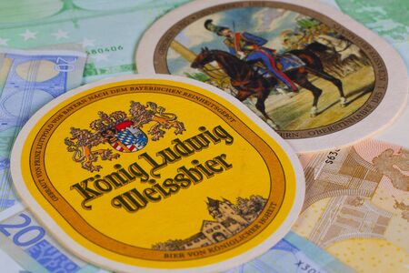 exists: Berlin,Germany-January 12,2015: Beermats from Konig Ludwig beer and eur banknotes..The brewery as it exists today was opened in 1870