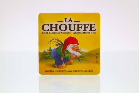 brasserie: Germany,Berlin - January 7,2015:Beermat from La Choufee beer on a glass table.La Chouffe is a Belgian Strong Pale Ale style beer brewed by Brasserie d Achouffe in Achouffe, Belgium.