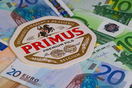 primus: Berlin,Germany-January 12,2015: Beermat from Primus beer and EUR money.Primus is a Euro Pale Lager style beer brewed by Brouwerij Haacht NV in Boortmeerbeek, Belgium. Editorial