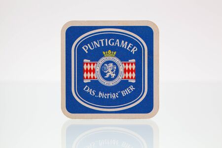 illustrative material: Germany,Berlin - January 7,2015:Beermat from Puntigamer beer on a glass table.Puntigamer is a Euro Pale Lager style beer brewed by Brauerei Puntigam  in Graz, Austria.