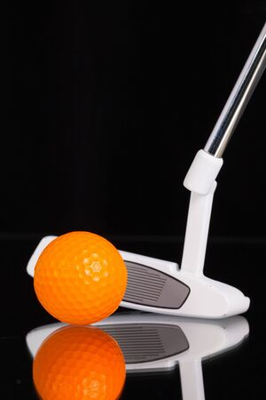 putter: Golf putter and different golf equipments on the black glass desk Stock Photo