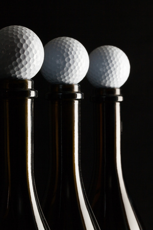Silhouettes of elegant wine bottles with golf balls on a black background