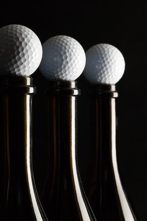 Siluety elegantních lahví vína s golfové míčky na černém pozadí