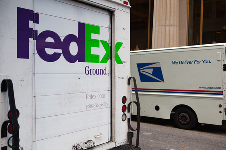 usps: New York,USA- July 29,2013: FedEx and USPS cars on the same street in New York.FedEx is an American global courier delivery services company.The USPS is the operator of the largest civilian vehicle fleet in the world. Editorial