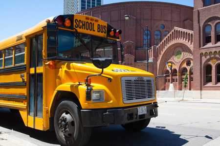 Chicago,USA - July 12,2013 : Typical american yellow school bus in front of the D.L.Moody memorial church and sunday school in Chicago