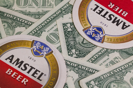amstel: England,London - November 11, 2014:Beermats from Amstel beer and US dollars. Amstel Brewery is a Dutch brewery founded in 1870 on the Mauritskade in Amsterdam