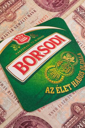 cs: Budapest,Hungary - January 7,2015:Borsodi beermat and old Hungarian money. Borsod Brewery or Brewery of Borsod is a brewery located in the village of Bőcs, near Miskolc, the capital of Borsod-Abaúj-Zemplén county in northeastern Hungary. Editorial