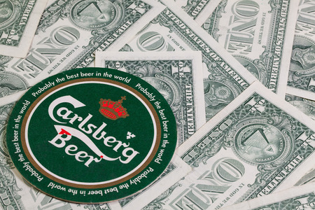 carlsberg: England, London - November 11, 2014:Beermat from Carlsberg beer and US dollars.The Carlsberg is a Danish brewing company founded in 1847 by J. C. Jacobsen with headquarters located in Copenhagen,Denmark