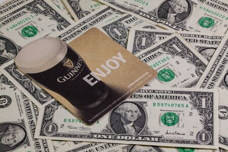 guinness beer: England,London - November 11, 2014:Beermats from Guinness beer and US dollars.Guinness is an Irish dry stout that originated in the brewery of Arthur Guinness (1725–1803) at St. Jamess Gate, Dublin. Editorial
