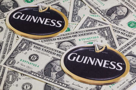 st jamess: England,London - November 11, 2014:Beermats from Guinness beer and US dollars.Guinness is an Irish dry stout that originated in the brewery of Arthur Guinness (1725–1803) at St. Jamess Gate, Dublin. Editorial