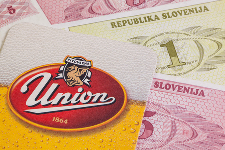 nonalcoholic beer: Croatia,Novigrad - August 13,2014: Beermat from Union beer and Slovenia money.The Union Brewery Ljubljana, Slovenia produces beer, refreshing non-alcoholic drinks and non-alcoholic drinks.
