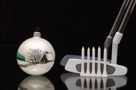 christmas golf: Christmas decoration and two golf putters  on a glass desk Stock Photo