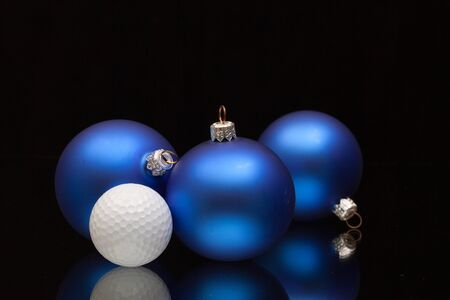 christmas golf: Blue Christmas decoration a golf balls on a black glass desk