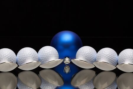 christmas golf: Blue Christmas decoration and six spoons with golf balls on a black glass desk Stock Photo