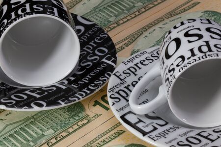 two us dollar: Two empty coffee cups lying on US dollar banknotes