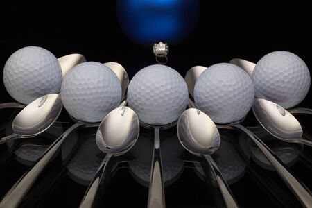 christmas golf: Blue Christmas decoration, golf balls and nine spoons on a black glass desk